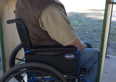 main in wheelchair shooting a pistol