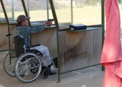 man in wheelchair shooting a gun at fraser coast pistol club
