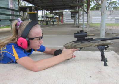 young girl lying on the ground aiming a gun
